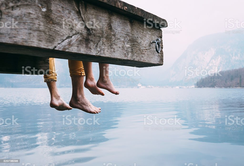 Father and son on wooden pier on mountain lake stock photo
