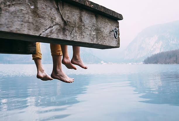 Vater und Sohn auf dem hölzernen pier am Bergsee – Foto