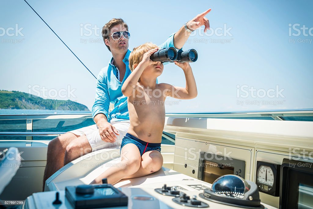 Father and son on yacht stock photo