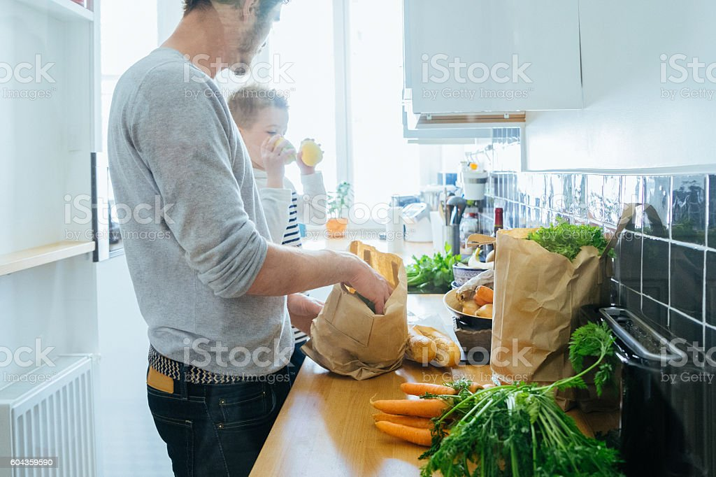 Father And Son Organizing Groceries In The Kitchen stock photo