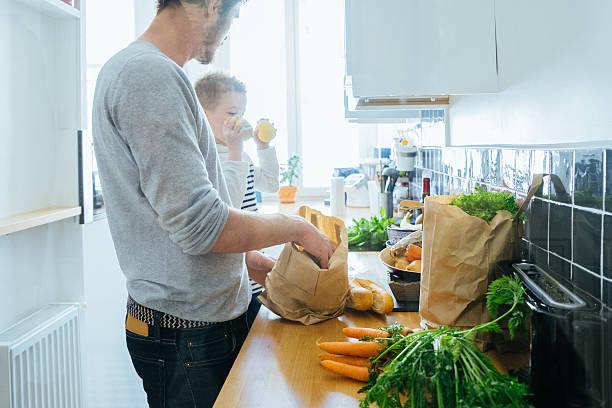 padre e figlio organizzazione di generi alimentari in cucina - grocery home foto e immagini stock