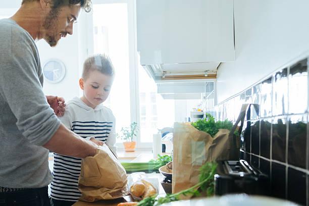 padre e hijo en la cocina organización de comestibles - padre que se queda en casa fotografías e imágenes de stock