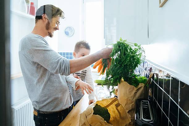 vater und sohn organisation lebensmittel in der küche - hausmannskost stock-fotos und bilder