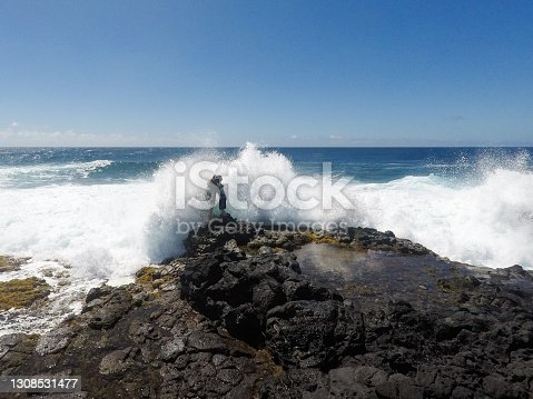 istock Father and son overtaken by waves 1308531477
