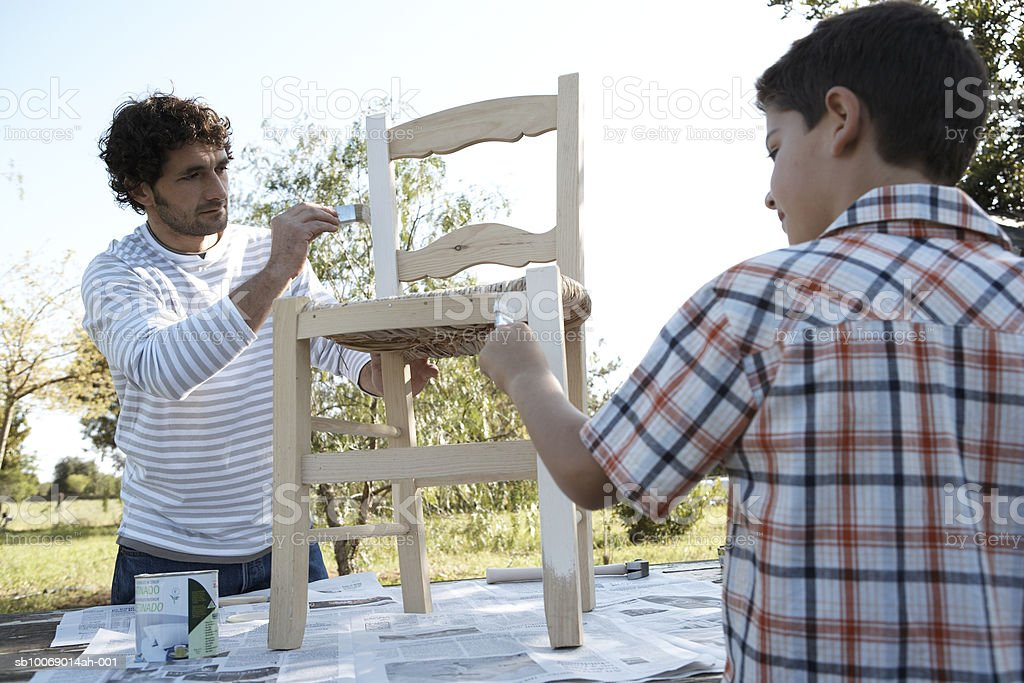 Father and son (8-9) painting chair outdoors royalty-free stock photo