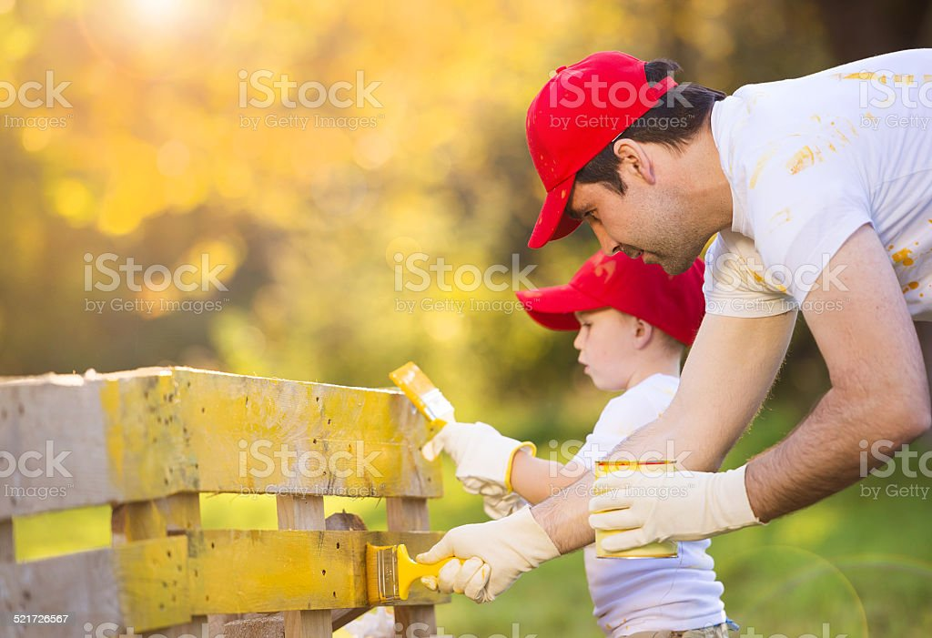 Father and son painting fence stock photo