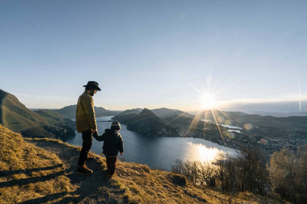 Father and son pause at edge of trail, mountainside stock photo