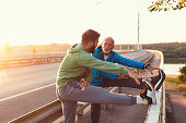 Happy father and son exercising together outdoors on big modern bridge.