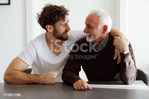 70-year-old father is sitting at the table with his 30-year-old son and smiling.