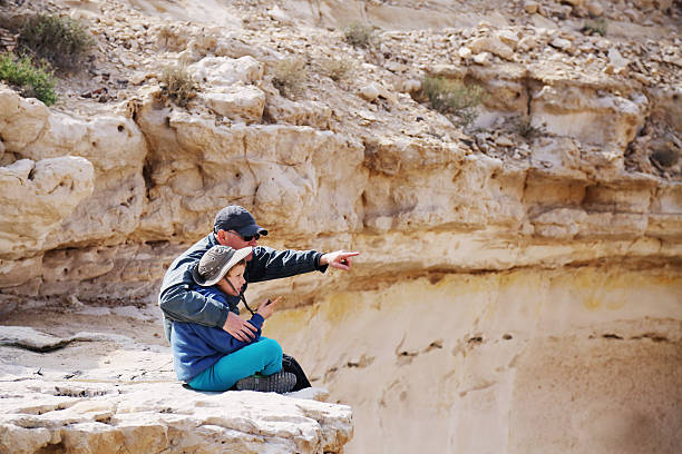 father and son father and son hiking together in the desert negev stock pictures, royalty-free photos & images