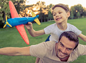 Portrait of handsome happy father and his little son smiling while playing outdoors. Boy is holding a toy plane, sitting pickaback