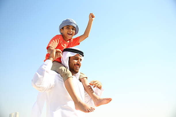 Father and Son Arabian family playing in the beach. arabia stock pictures, royalty-free photos & images