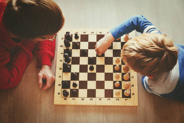 father and son play chess stock photo
