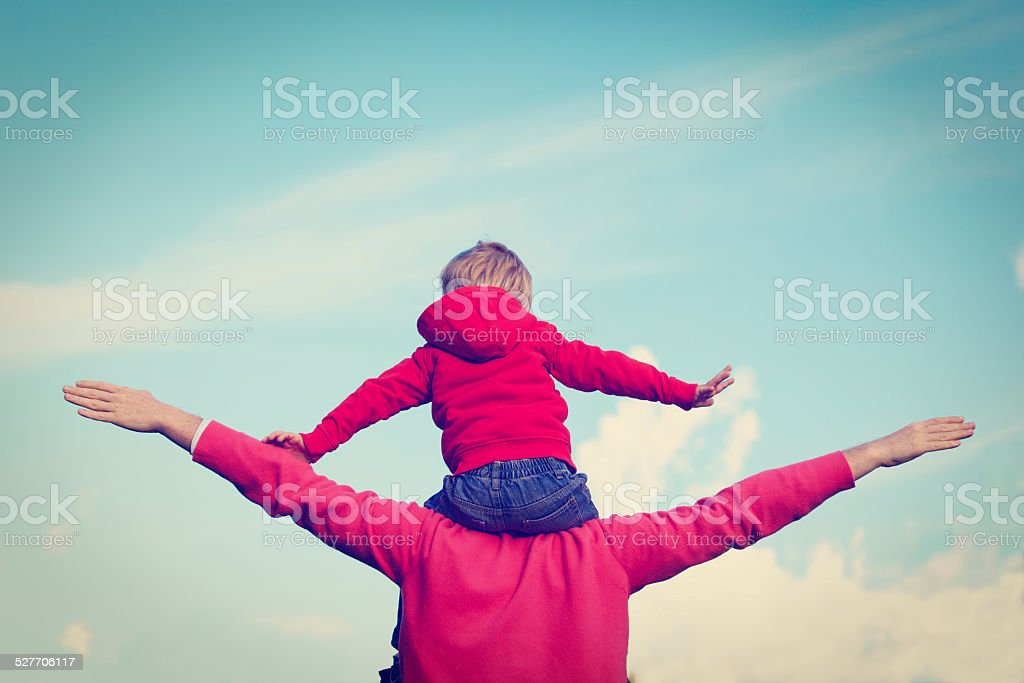 father and son play on sky stock photo