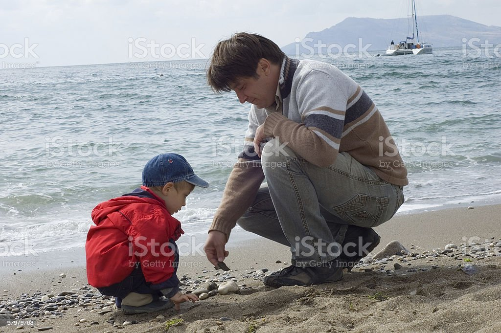 father and son play on the beach royalty-free stock photo