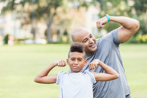 Father and son playfully flexing muscles