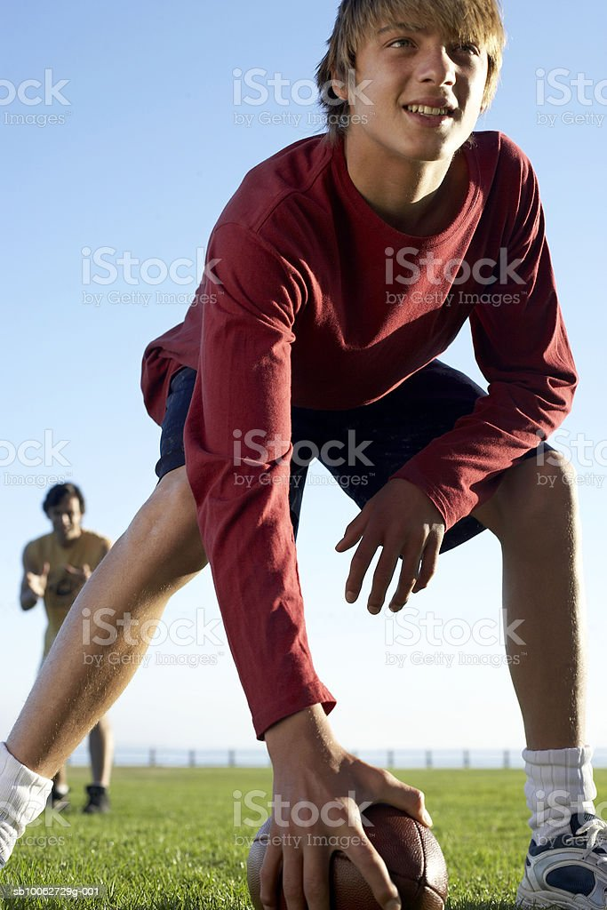 Father and son (14-15) playing American football, low angle view 免版稅 stock photo