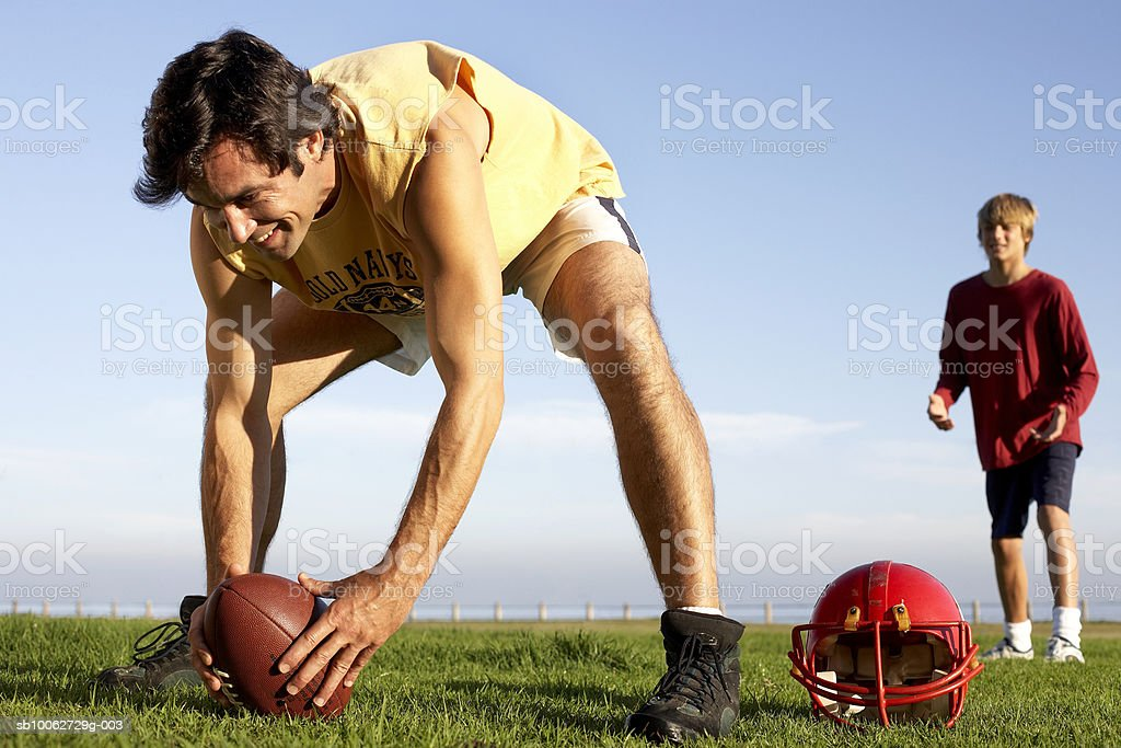 Father and son (14-15) playing American football royalty-free stock photo