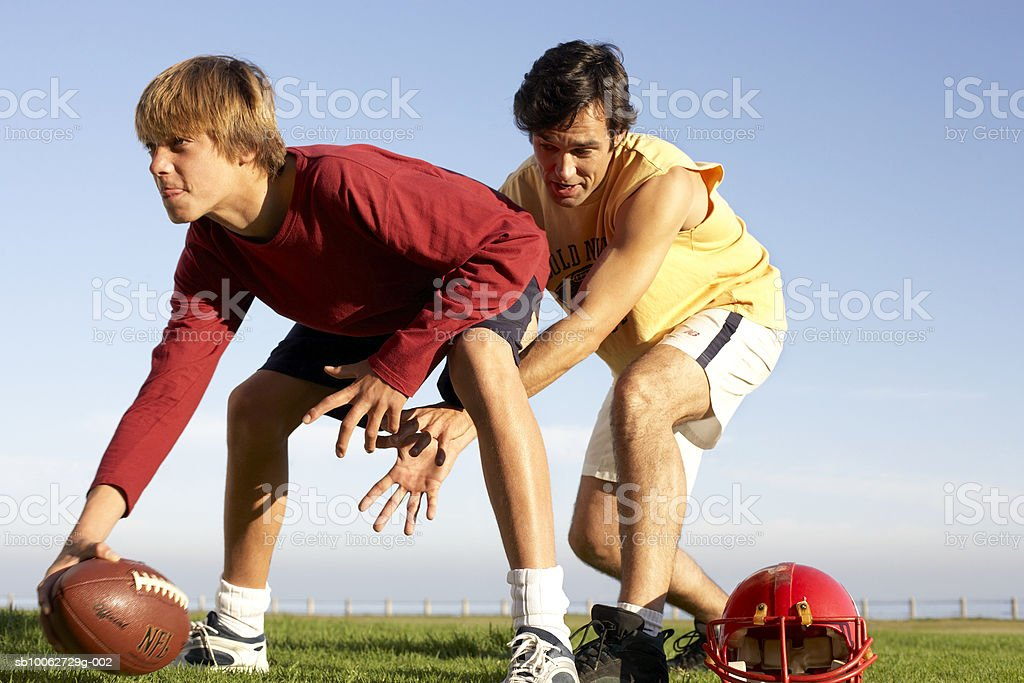 Father and son (14-15) playing American football, side view foto de stock libre de derechos