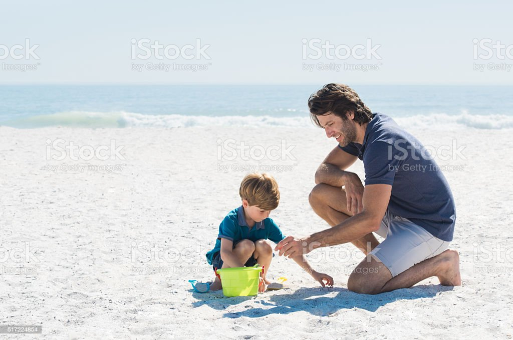 Father and son playing at beach stock photo