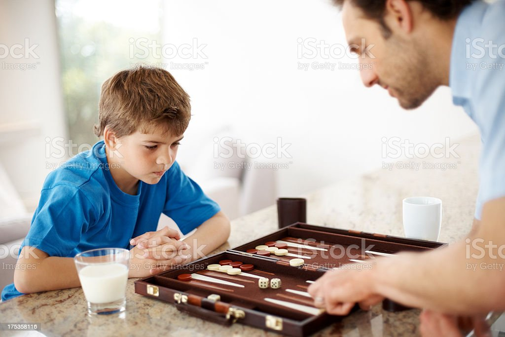Father and son playing backgammon game in kitchen stock photo