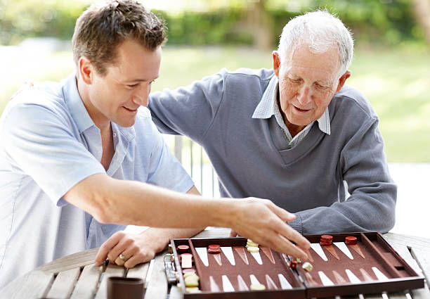 father and son playing backgammon in a park - backgammon stock pictures, royalty-free photos & images