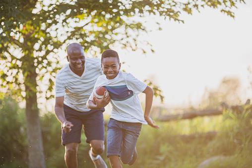 A kid around 7 years old and his dad laugh together while playing football on a lawn in the summertime.
