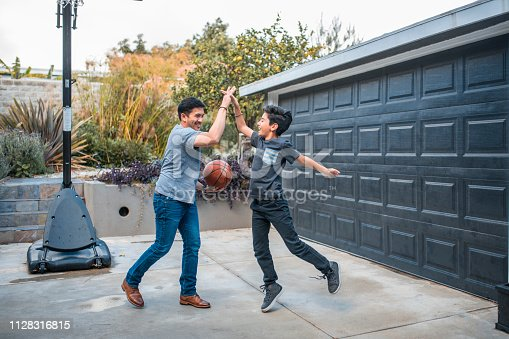 istock Father and son playing basketball at court 1128316815