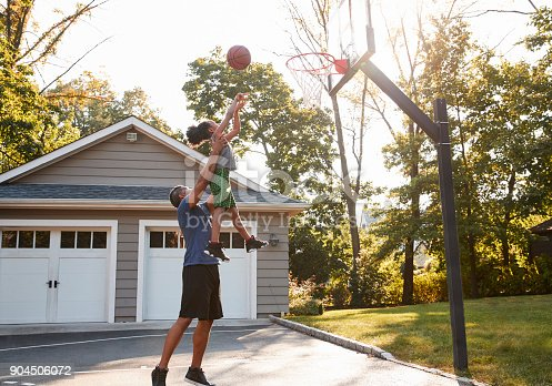 istock Father And Son Playing Basketball On Driveway At Home 904506072