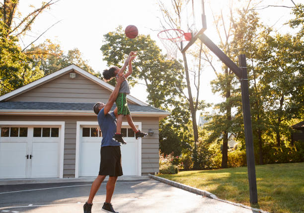 Father And Son Playing Basketball On Driveway At Home - foto stock