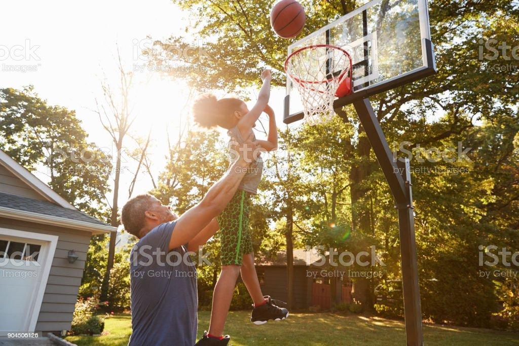 Vater und Sohn spielen Basketball auf Einfahrt zu Hause – Foto