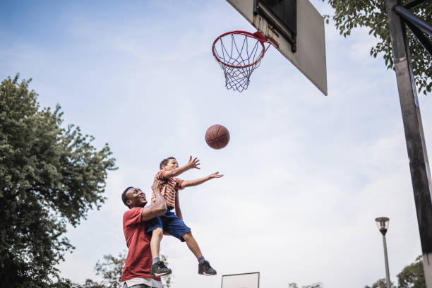 Father and son playing basketball Father and son playing basketball. Belgrade, Serbia jump shot stock pictures, royalty-free photos & images
