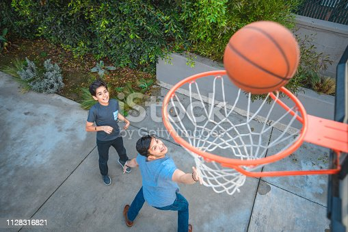 Father and son playing basketball. High angle view of family is looking at ball over hoop. They are having fun during weekend.