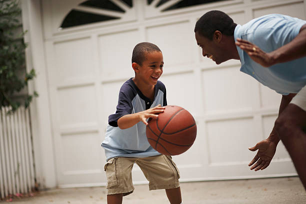 Father and son playing basketball stock photo