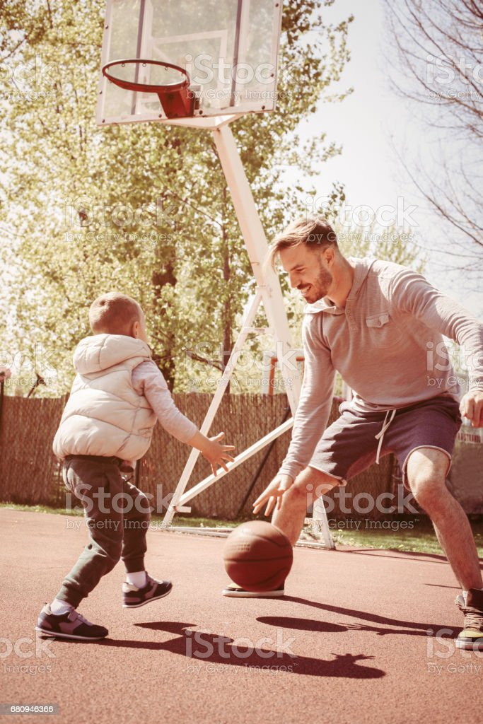 Father and son playing basketball. stock photo