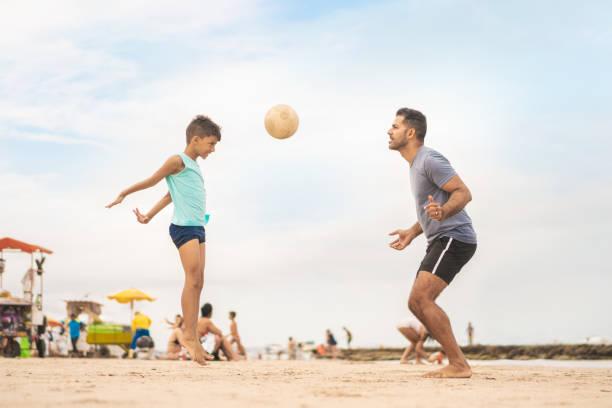 pai e filho que jogam o futebol da praia em porto de galinhas no estado de pernambuco, brasil. - futebol de areia - fotografias e filmes do acervo