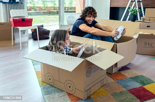 istock Father and son playing car racing with cardboard boxes 1086231958