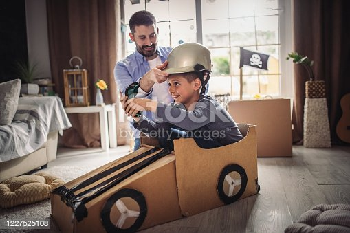 942256562 istock photo Father and son playing car racing with cardboard boxes 1227525108