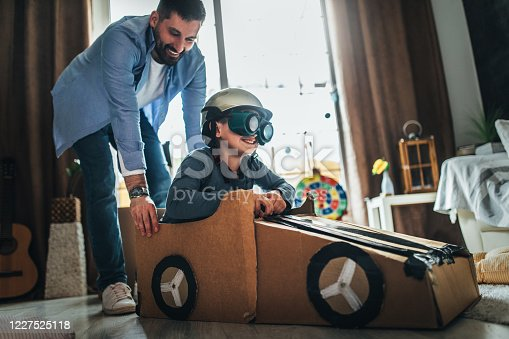 942256562 istock photo Father and son playing car racing with cardboard boxes 1227525118