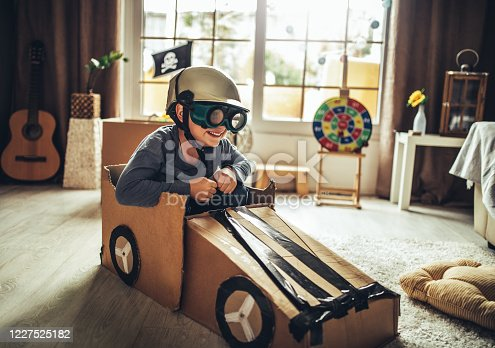 942256562 istock photo Father and son playing car racing with cardboard boxes 1227525182