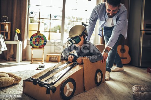 942256562 istock photo Father and son playing car racing with cardboard boxes 1227525206