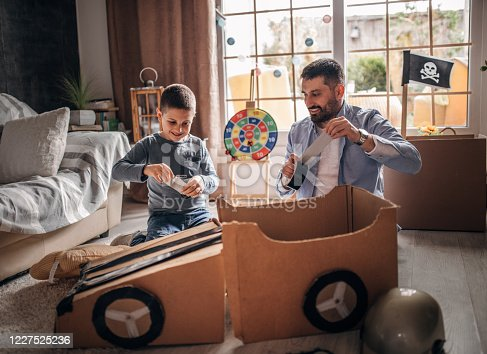 942256562 istock photo Father and son playing car racing with cardboard boxes 1227525236