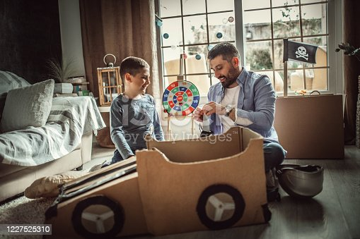 942256562 istock photo Father and son playing car racing with cardboard boxes 1227525310