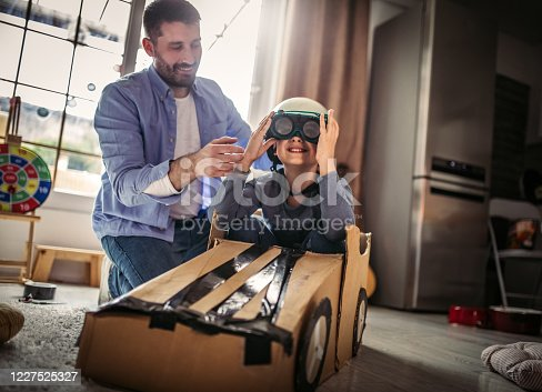 942256562 istock photo Father and son playing car racing with cardboard boxes 1227525327