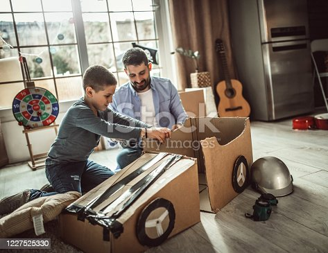 942256562 istock photo Father and son playing car racing with cardboard boxes 1227525330