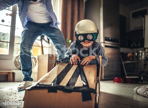942256562 istock photo Father and son playing car racing with cardboard boxes 1227525461