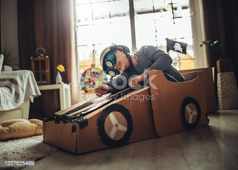 942256562 istock photo Father and son playing car racing with cardboard boxes 1227525469