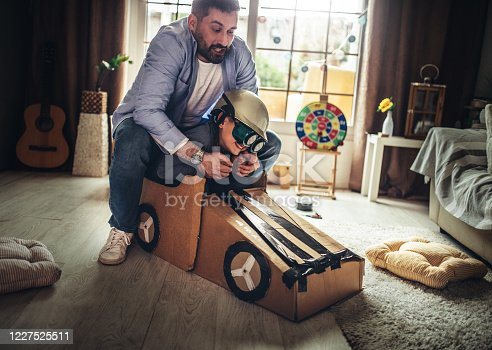 942256562 istock photo Father and son playing car racing with cardboard boxes 1227525511