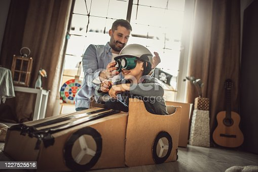 942256562 istock photo Father and son playing car racing with cardboard boxes 1227525516