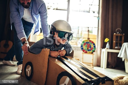 942256562 istock photo Father and son playing car racing with cardboard boxes 1227525517